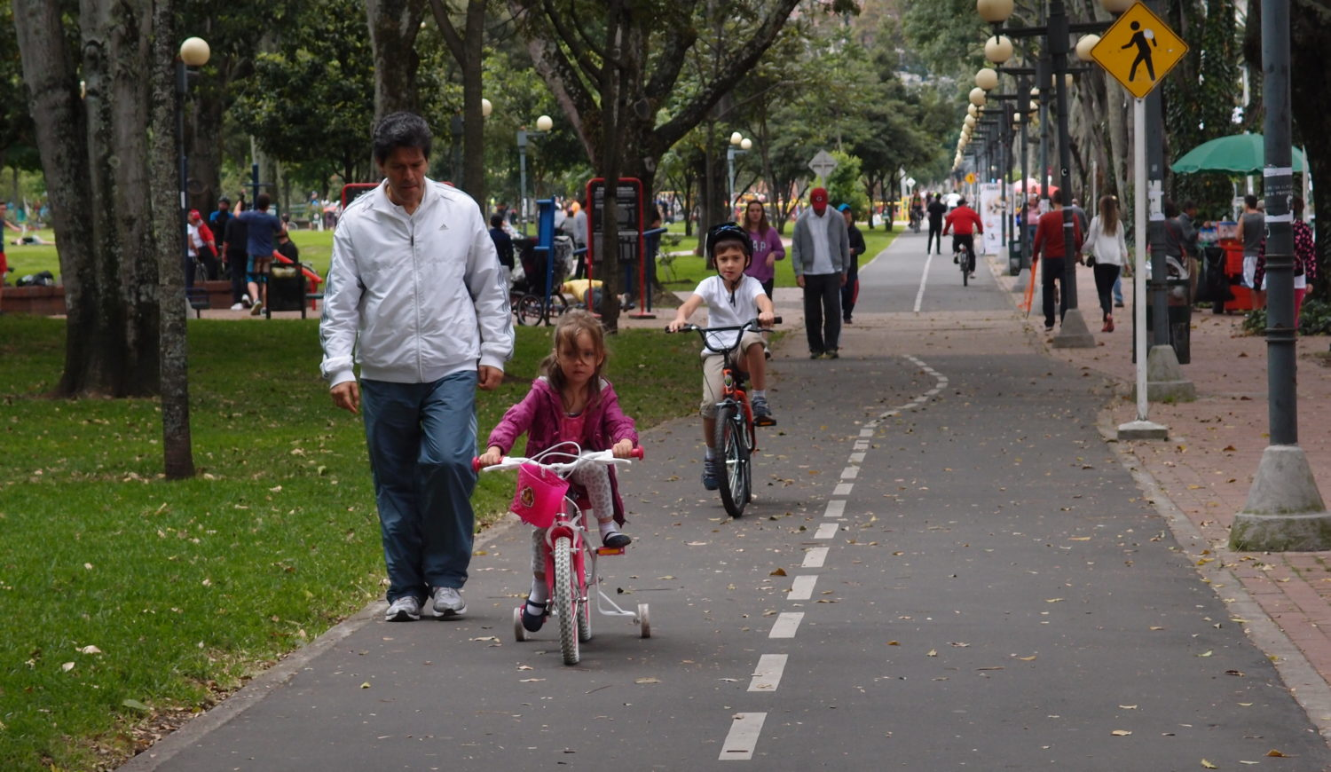 A man walking behind a young girl riding a bike in a bike path