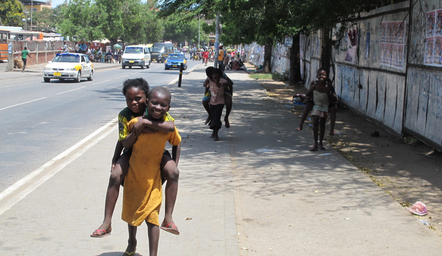Six children playing piggyback with each other, walking down a street in Accra