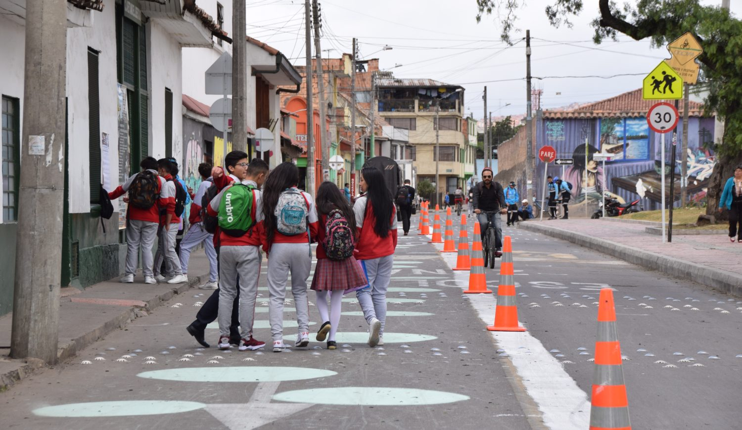 A group of teenagers walking down the street in Bogota