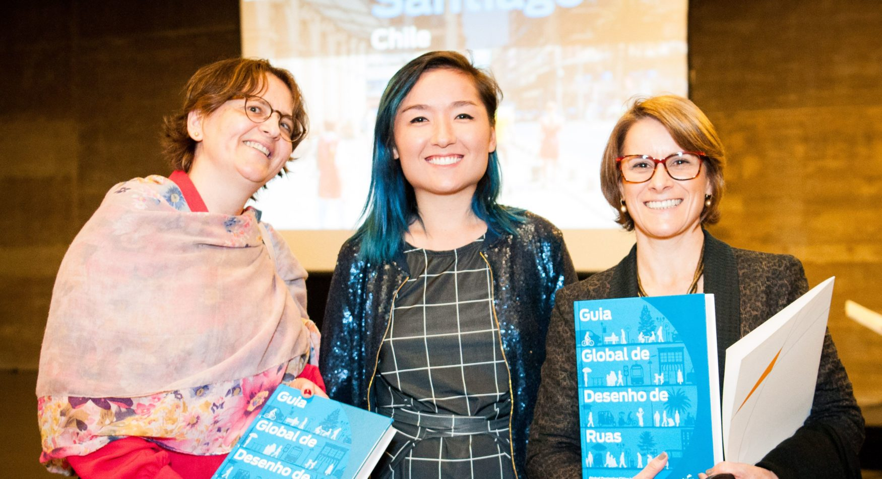 Three women holding the Portuguese translated Global Streets Design Guide