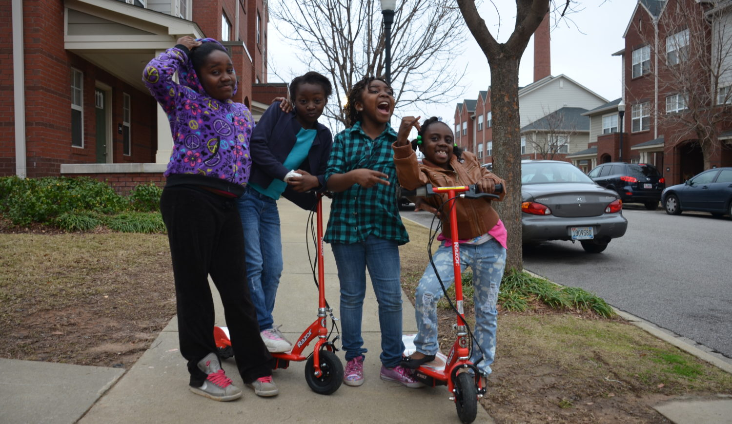 Four girls with two scooters playing on a sidewalk