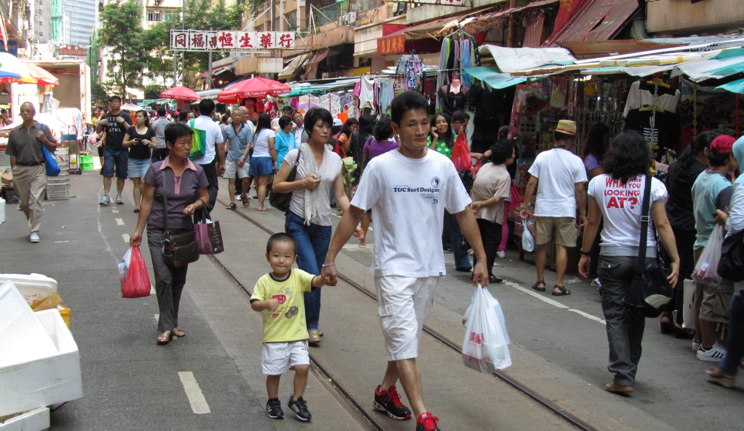 A man walking down a busy Hog Kong street holding the hand of a young child