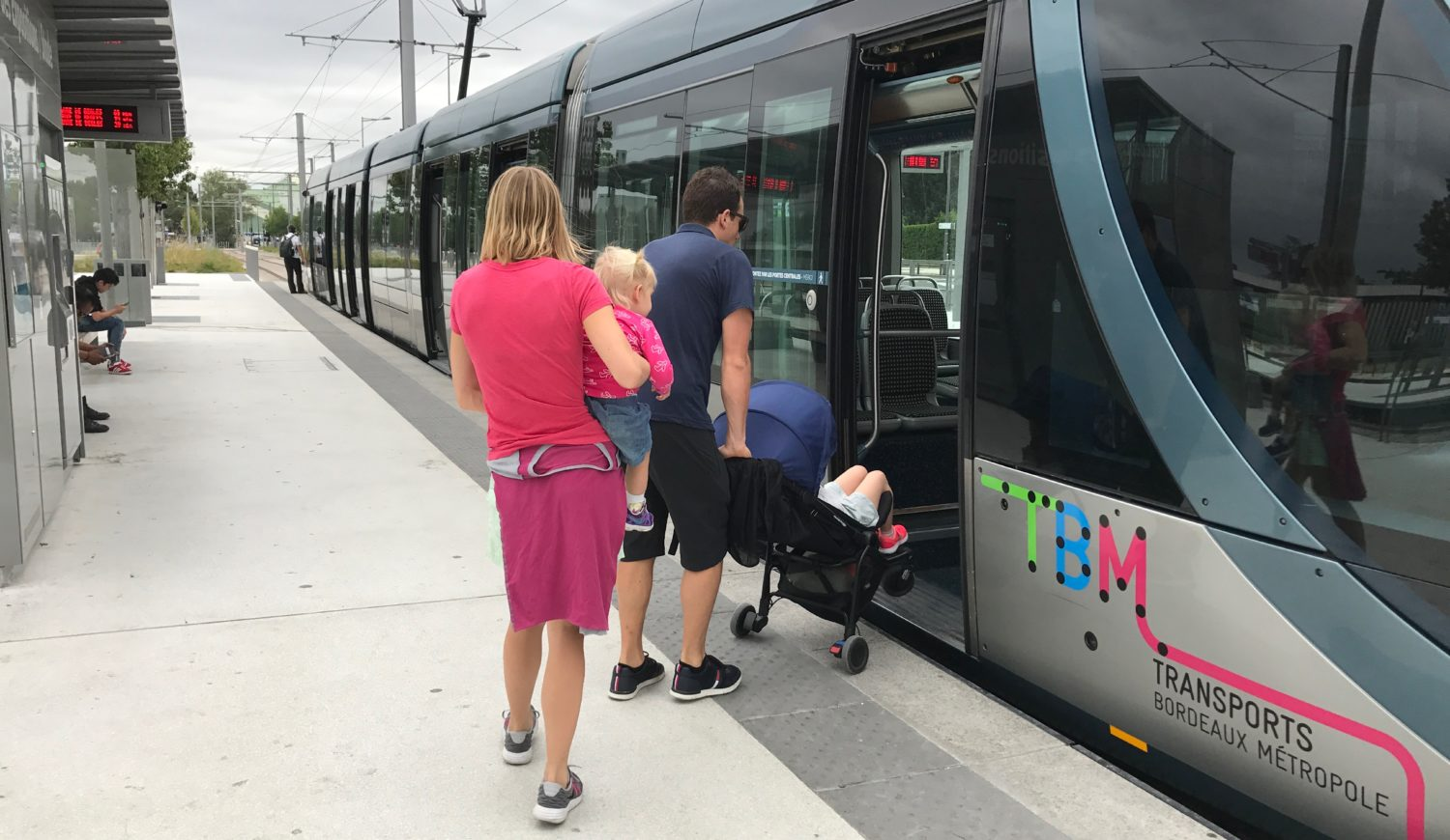 A man boarding a train with a stroller and a woman holding a small child walking behind him